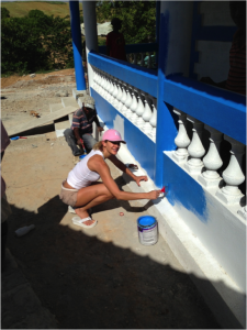 Christine with volunteers, painting the exterior of one of the buildings in  the new school.