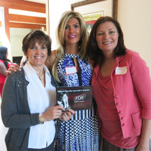 Representatives of Zoe Organization, Betsy Meenk, USA Regional Director, (left) and Program Services Manager, Marji Iacovetti pose with Christine (center) at the Ladies High Tea event.