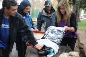 Mary Avanti, right, spreads shoes on a table at Lawrence Park as Eric Lantz, left,  and Donna Evans, second from left, look on.