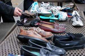 A homeless man looks over the shoes donated by Woodbridge resident Mary Avanti at Lawrence Park in Lodi on Thursday.